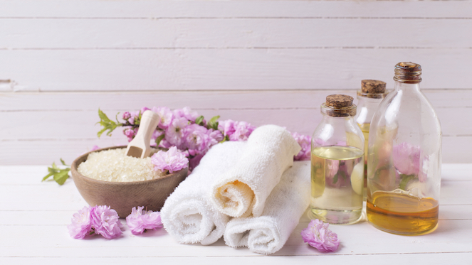Spa and wellness setting. Sea salt in bowl, towels and bottles with aroma oils on white wooden background. Selective focus is on towels.